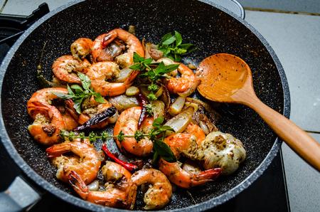 Garnalen geserveerd op een pan met verse kruiden