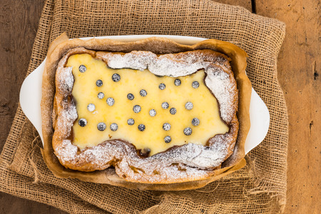 casserole dish: top view of eclair cake in casserole dish with blueberry on wood table