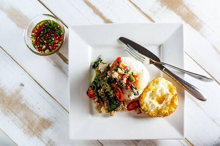 Thaise kruidig ??voedsel basilicum varkensvlees gebakken met rijst en gebakken ei en chili vissaus, Pad Kra Pao moo Stockfoto - 44293500