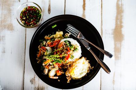 Thaise kruidig voedsel basilicum varkensvlees gebakken met rijst en gebakken ei en chili vissaus, Pad Kra Pao moo