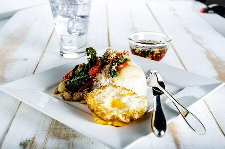 Thaise kruidig ??voedsel basilicum varkensvlees gebakken met rijst en gebakken ei en chili vissaus, Pad Kra Pao moo Stockfoto - 44293559