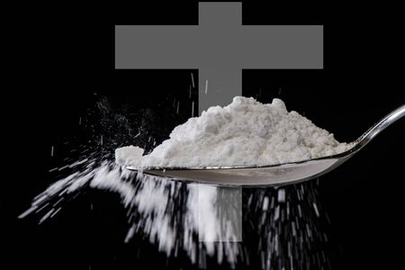 heroin: white powder in spoon like drug or medicine with a cross in background as sign for death Stock Photo