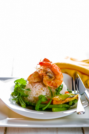 rice plate: Dish with shrimps rice and green asparagus in a white plate, white background and white wood table
