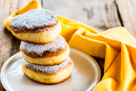 powdered: three delicious german doughnuts powdered with sugar on white plate