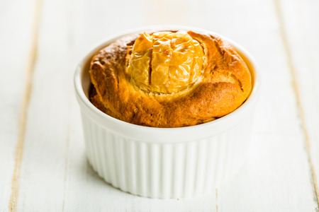 small cake: Small cake with apple in a ramekin on white wood table Stock Photo