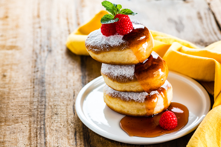 A stack of tree delicious german doughnuts powdered with sugar decorated with raspberry and raspberry sauce on white plate and yellow napkin