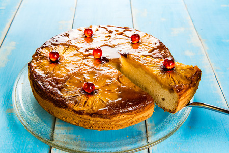 Upside down pineapple cake with caramel. A piece of cake is cut.