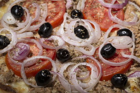 cebollas: pizza with onions, tuna, tomatoes and olives on wooden table