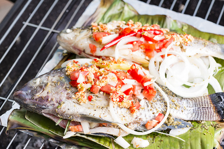prepared fish: Freshly prepared fish on barbecue with vegetables and lemon. The fish is on banana leaf
