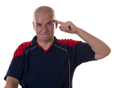 restrained: Single smart bald man in blue and red shirt with restrained grin pointing to his head with index finger over white background