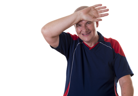 shaved head: Sweaty elderly man with shaved head and wearing blue shirt wipes forehead and smiles Stock Photo