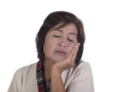 fatigued: Single exhausted mature woman with tired expression, eyes closed and chin in palm over white background Stock Photo