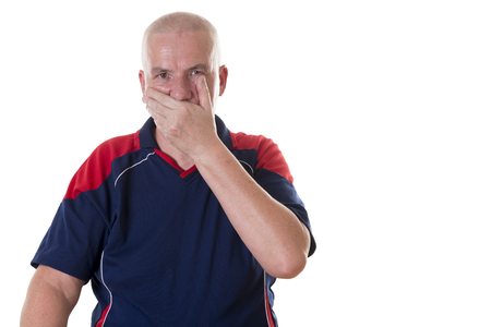 aghast: Aghast older man with shaved head in blue and red shirt holds one hand over his mouth against white background