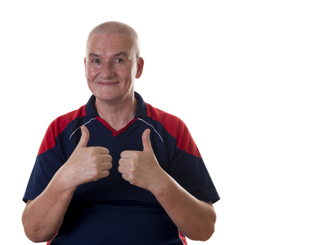 shaved head: Smiling single older man with shaved head and both hands with thumbs up wearing blue and red shirt over white background Stock Photo
