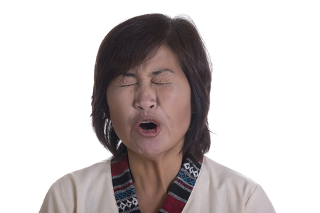 Single beautiful mature Asian woman yawning or yelling with mouth open and eyes shut tightly over white background