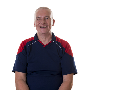 shaved head: Laughing single middle aged man with shaved head and blue and red shirt sitting over white background Stock Photo