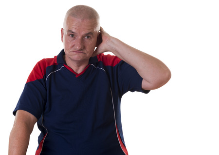 shaved head: Uncertain older man with shaved head and blue shirt scratches behind his ear with one hand Stock Photo