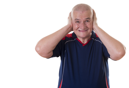 short sleeved: Solitary elderly man wearing short sleeved blue shirt cringes and covers ears with both hands