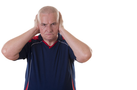 short sleeved: Angry aging bald man wearing short sleeved shirt frowns and presses hands to ears against light background Stock Photo