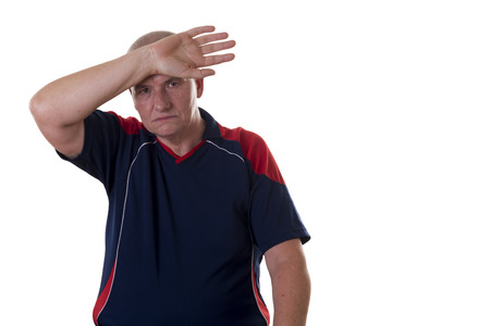 frowns: Lightheaded older man with blue and red shirt frowns while pressing arm to forehead Stock Photo