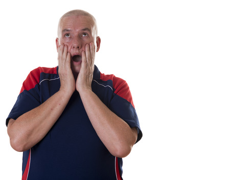 rolling up: Overwhelmed single middle aged man with hands on face, mouth wide open and eyes rolling up over white background Stock Photo