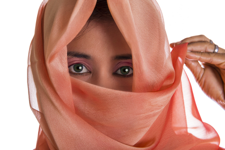 eyes hidden: Close up view on eyes peering from partially hidden face of woman in pink veil with hand holding one end over white background