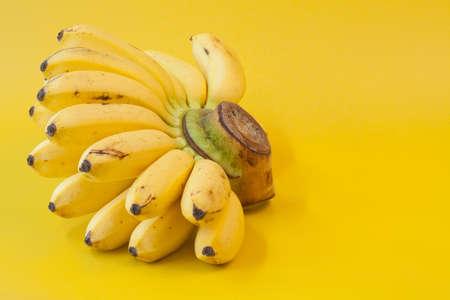 Yelloww bananas on yellow background photo