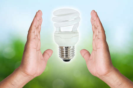 Two hand holding Fluorescent light bulb on nature background photo