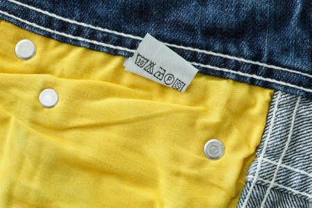 Laundry advice care symbols on blue jeans Stock Photo - 14742773