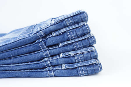 bluejeans: Stack of blue jeans isolated on white background Stock Photo
