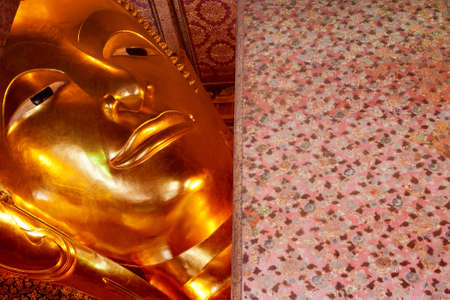 Reclining Buddha gold statue face. Wat Pho, Bangkok, Thailand photo