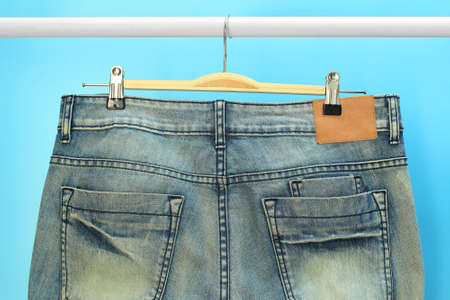 trouser: Blue jeans trouser hang on hanger Stock Photo