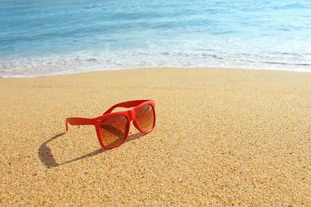 gafas de sol: Gafas de sol rojas en la playa Foto de archivo