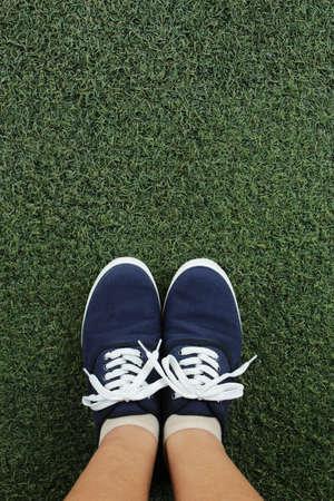 teen feet: Canvas sneakers on grass