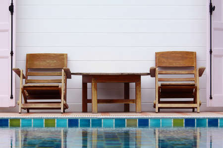 Wooden chair on ground beside swimming pool Stock Photo