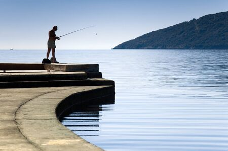 Lonely silhouette  of a fisherman standing. Hot summer day at city moorage Stock Photo - 4526097
