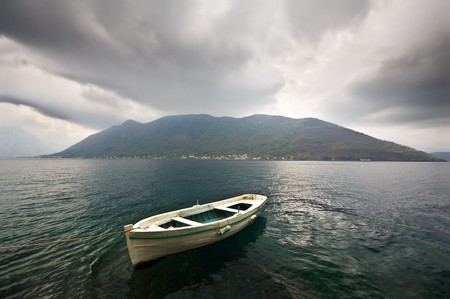 A boat tied with a rope. Storm beginning, dark clouds above, strong wind, a distant misty island on the background. photo