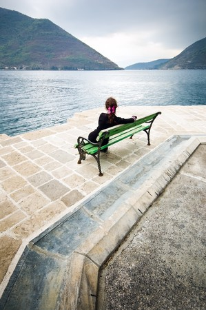 mujeres pensando: Una ni�a sentada en un banco al lado de la orilla del mar, pensando o esperando algo