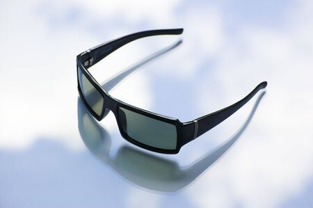 clody: Black sunglasses wiht a clody blue sky on the background