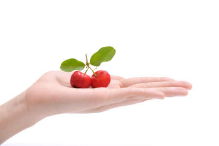 Barbados cherry fruit on women hand isolated on white background.