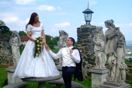 a bridal couple with statues photo