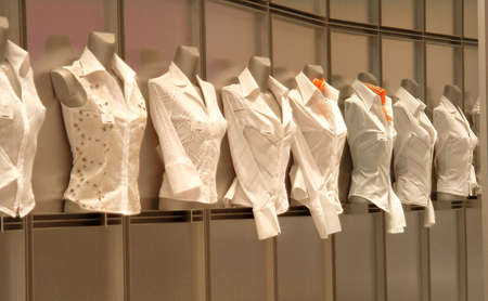 eight white blouses in shopwindow Stock Photo