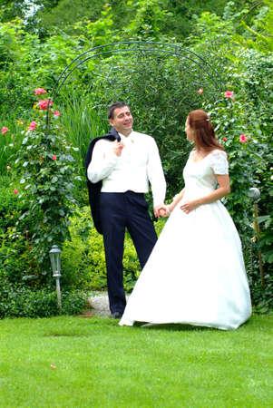 embracement: a marriage  pair stannding in a green garden