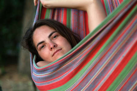 a young woman is lying in a couloured hammock