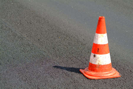 brindled: a red white brindled traffic cone on street Stock Photo