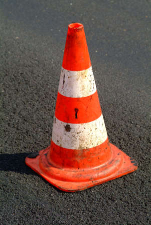 dangerouse: a red white brindled traffic cone on street Stock Photo