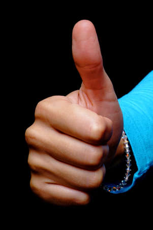 a young woman holds her thumb up