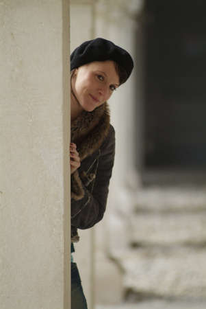 a  young woman leans at a pillar