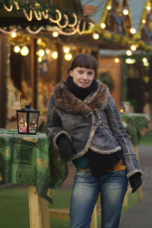 a dark haired woman drinks glogg at the market stall photo