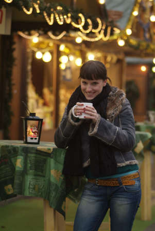 a dark haired woman drinks glogg at the market stall